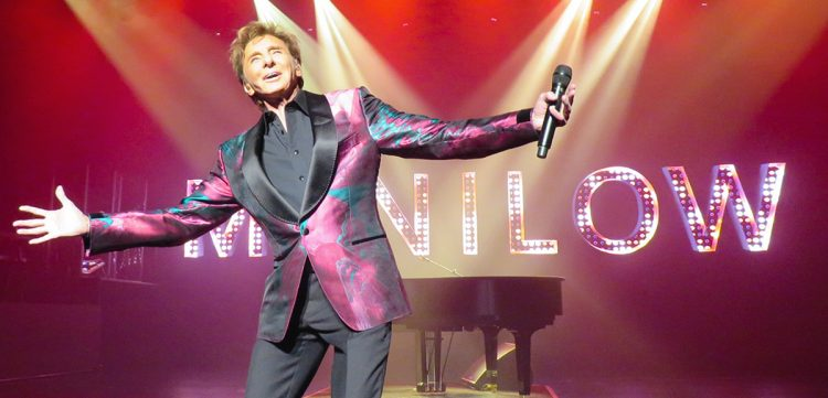 Barry Manilow on stage with his arms stretched out.